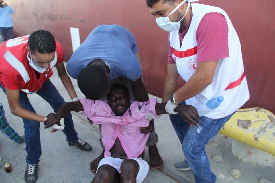 A survivor faints as he is brought to shore by volunteers with the Libya Red Crescent and a coastguard official. Photo: LRC