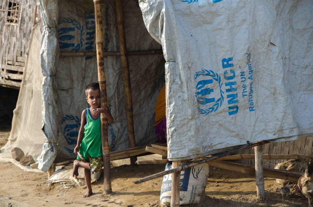 A young Rohingya boy stands outside an ad-hoc shelter constructed from bamboo and a tarpaulin provided by the UN refugee agency, in Say Tha Mar Gyi IDP camp, near Sittwe, Myanmar, on May 26, 2015.