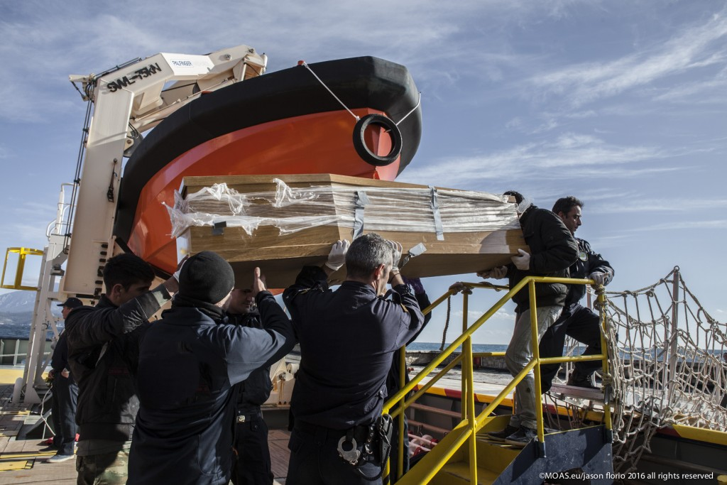Police officers lowering the coffin containing the bodies of the three children. Photo: Jason Florio/MOAS