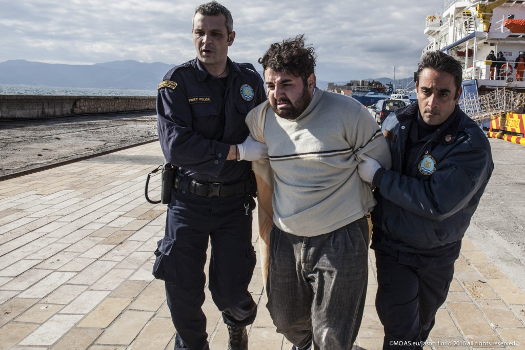 Suspected smuggler Ak Oskart being taken away by police in Samos, Greece. Photo: Jason Florio/MOAS.