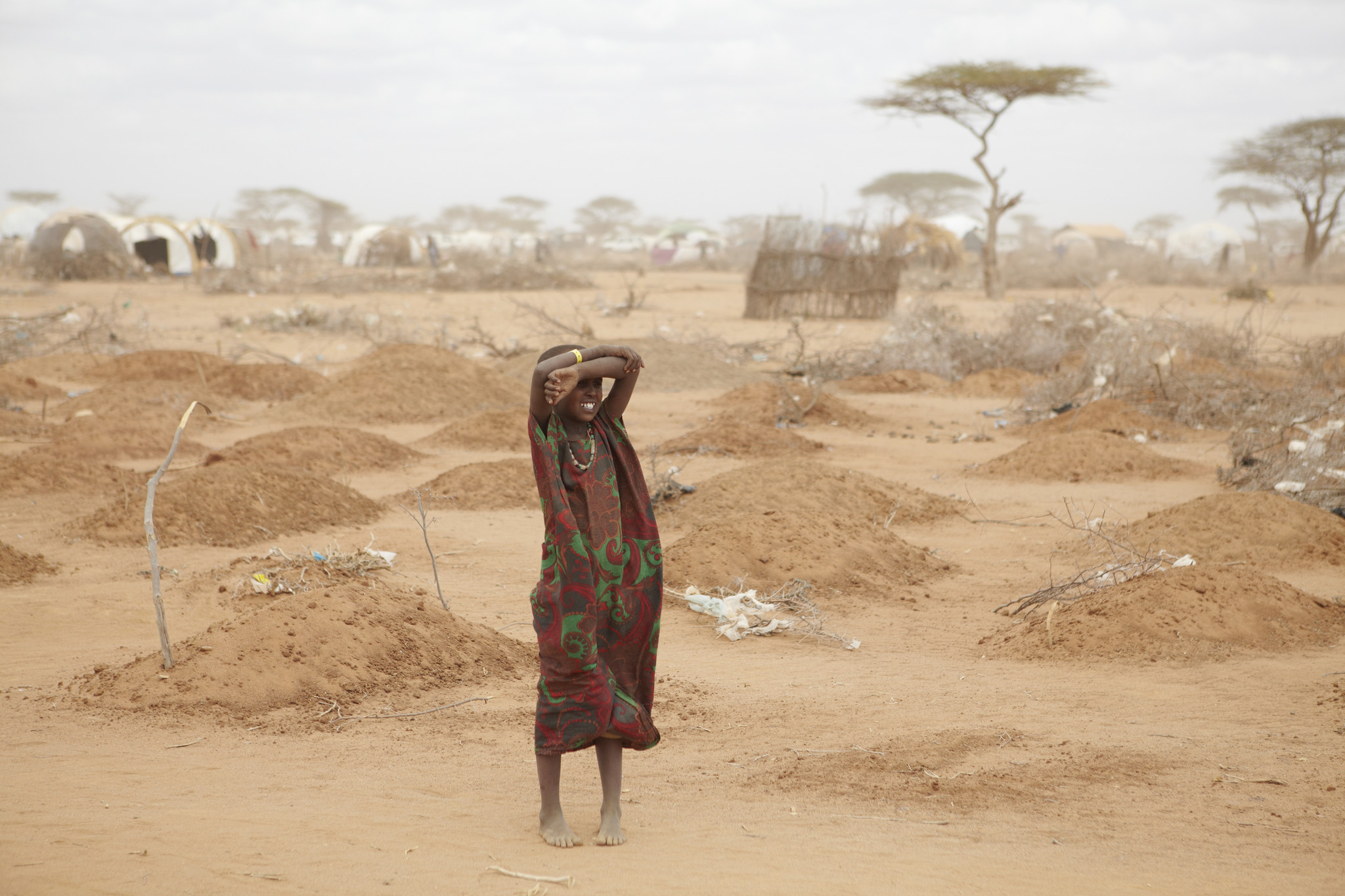 A young girl stands amid the freshly made graves of 70 children, many of whom died of malnutrition, outside Dadaab refugee camp. Photo: Andy Hall/Oxfam.
