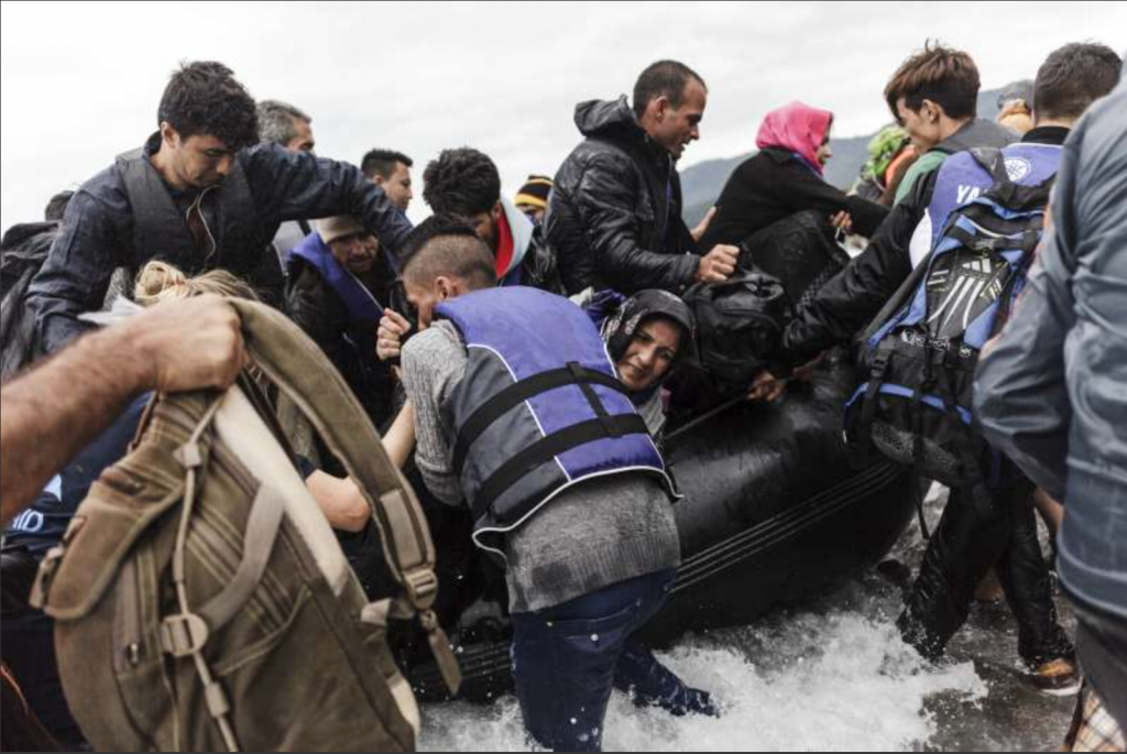 A group of refugees disembark an inflatable boat after reaching the Greek island of Lesvos. Photo: UNHCR Achilleas Zavallis