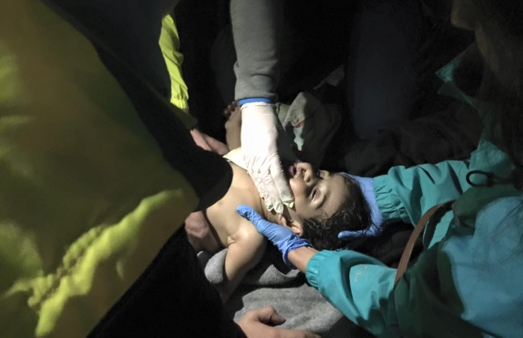 A girl being resuscitated by paramedics after being rescued off Lesvos.