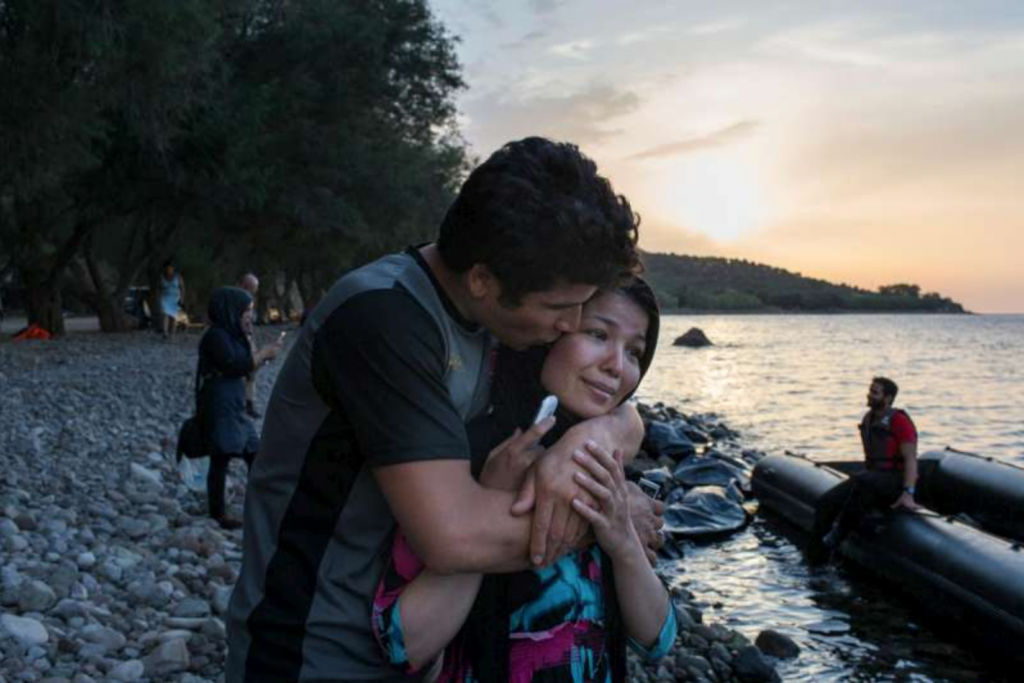 An Afghan refugee kisses his wife after they told relatives they had arrived safely on the Greek island of Lesvos. Photo: UNHCR: I. Priclett