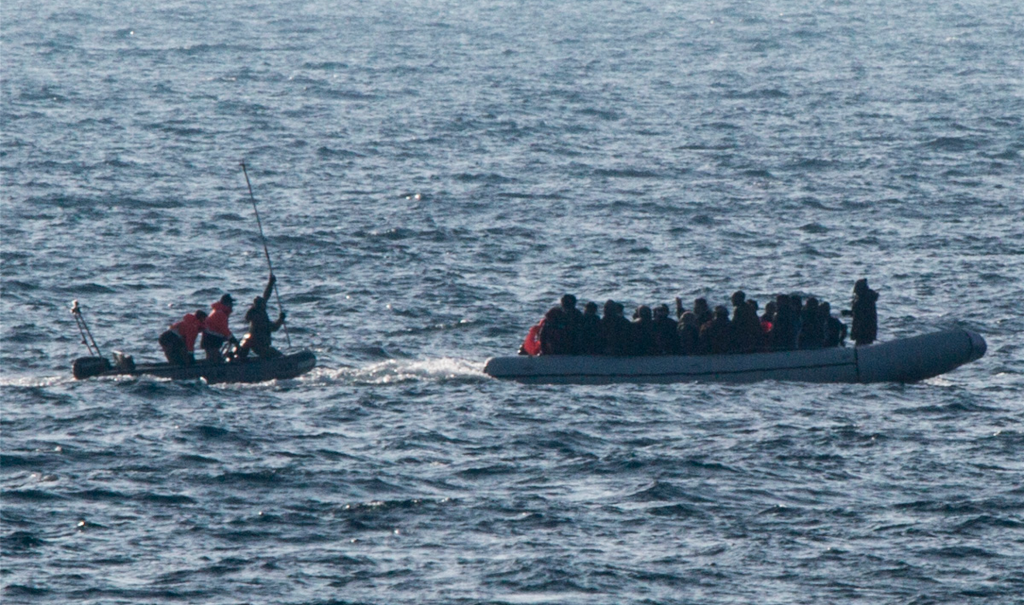 A Turkish coast guard about to strike the back of a migrant dinghy with 40 people on board, including 15 children. Photo: Jason Florio